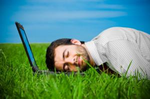 business man sleeping on laptop in the field